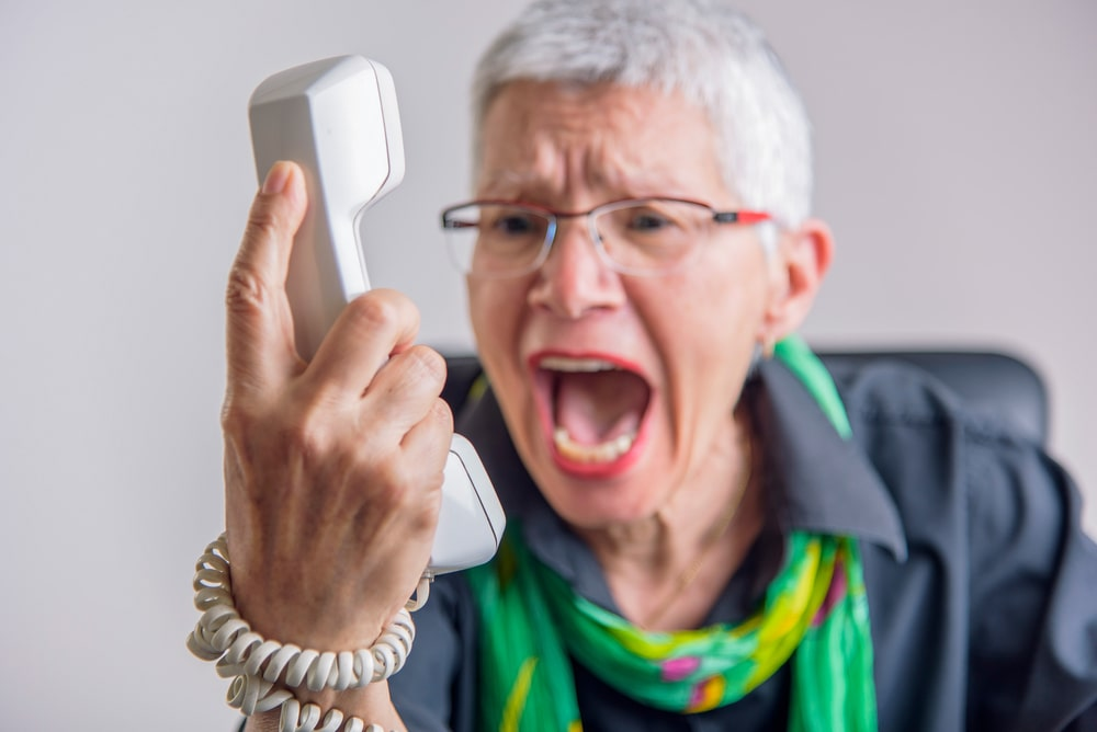 Terrible service, angry senior woman yelling at phone