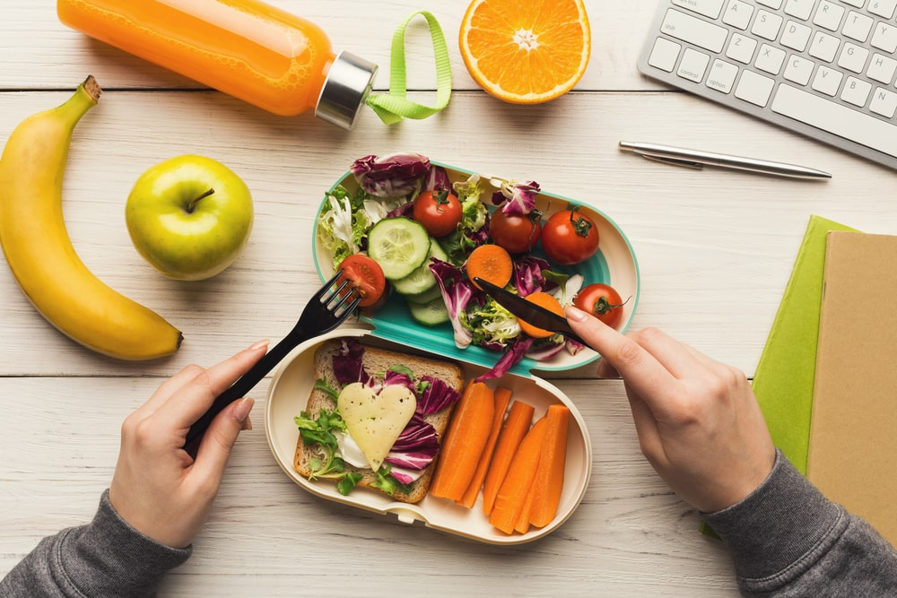 Woman eating healthy dinner from lunch box