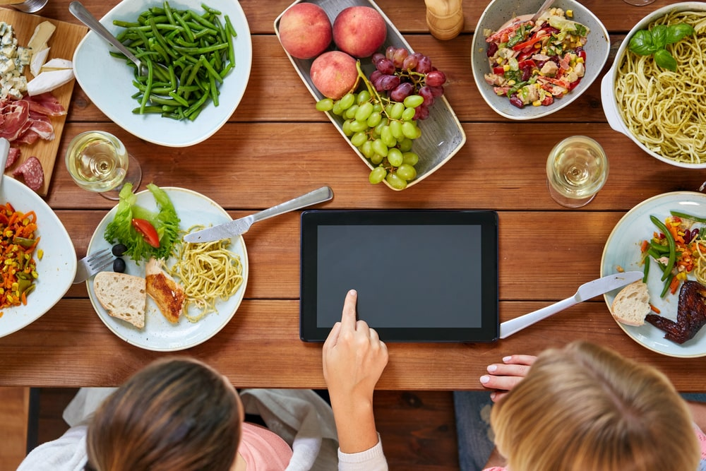 Women with tablet pc at table full of food