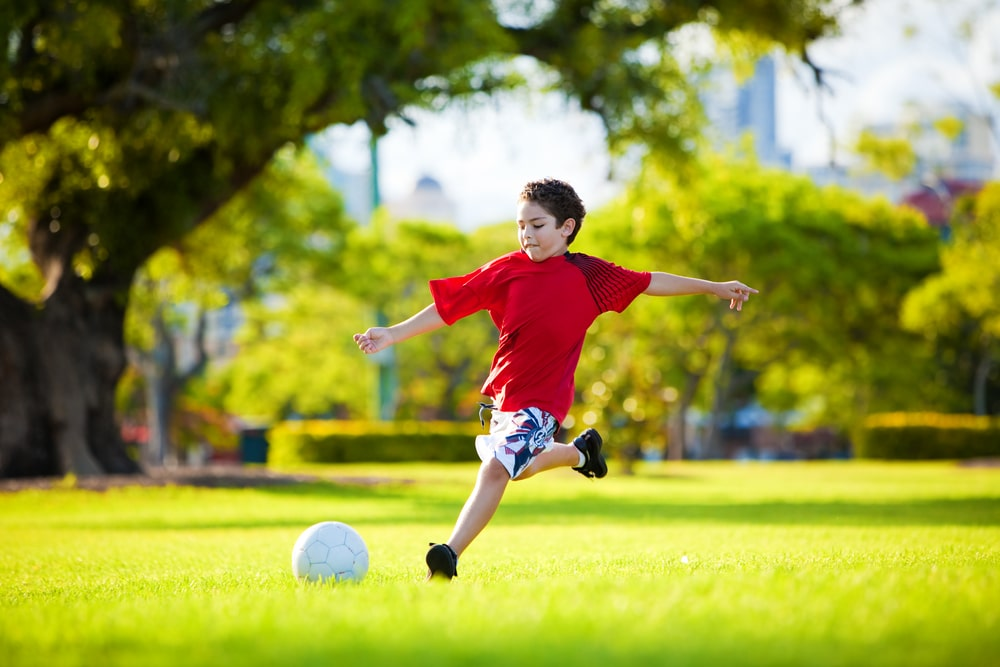 active boy playing soccer