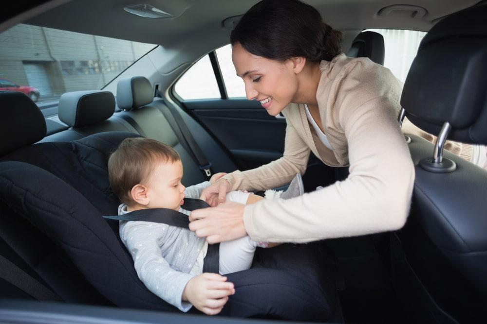 mother adjusting strap of infant car seat